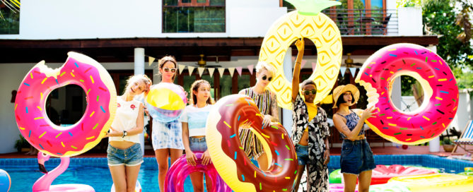 Group of diverse friends holding inflatable tubes by the pool