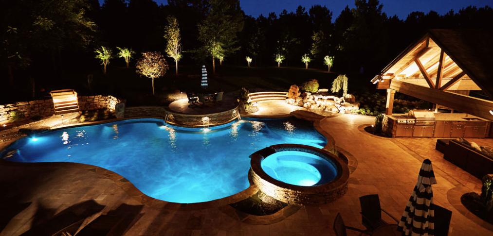 night time around backyard pool with landscape lighting