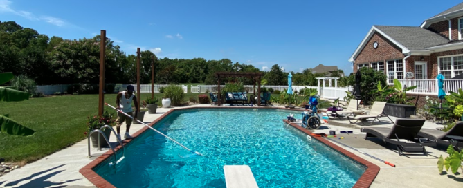 island pool services employee cleaning pool